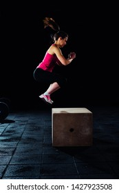 Young woman box jumping at a crossfit style gym
