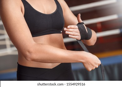 Young woman boxer putting on bandage tape around wrist near boxing ring close-up