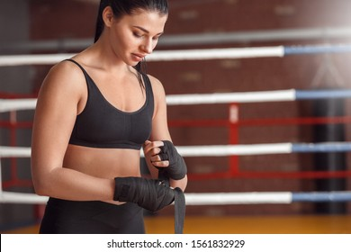 Young woman boxer putting on bandage tape around hands exercise standing near boxing ring smiling concentrated