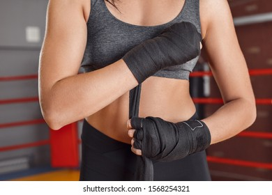 Young woman boxer putting on bandage tape around wrist standing on boxing ring close-up