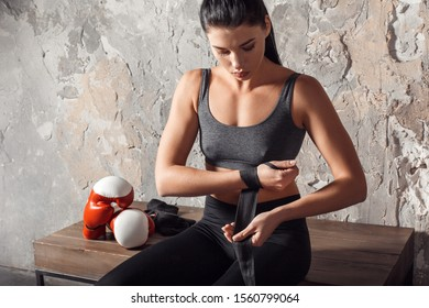 Young woman boxer sitting on bench before boxing exercise wrapping bandage tape around hand looking down pensive