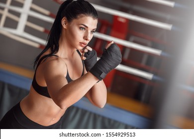 Young woman boxer wearing bandage tape around hands exercise hit standing near boxing ring concentrated