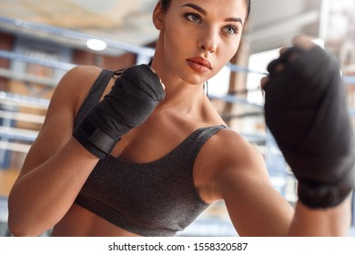 Young woman boxer wearing bandage tape around hands exercise kick standing near boxing ring serious close-up