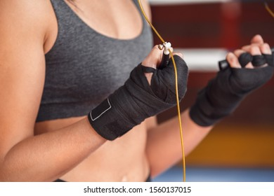 Young woman boxer wearing bandage tape exercise standing near boxing ring holding jump rope body close-up
