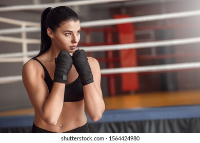 Young woman boxer wearing bandage tape around hands ready to exercise standing near boxing ring looking aside motivated