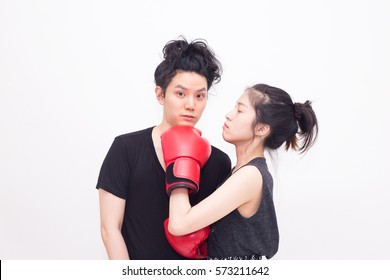 Young woman with boxing gloves fighting and punching the man or her boyfriend (Couple fighting or family problem concept), isolated on white background