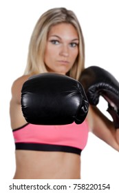 Young woman boxing and throwing a punch. Shot on a white background Note: Selective focus on the boxing glove in the foreground