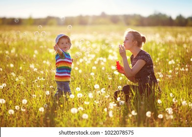 Young woman with a boy blowing bubbles. Mother and son having fun on dandelion field in nature in summer evening