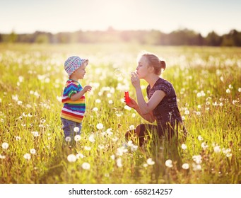 Young woman with a boy blowing bubbles. Mother and son having fun on dandelion field