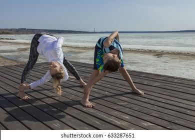 Young woman and boy doing wide legged Forward Bend, twist variation. Prasarita Padottanasana yoga pose.