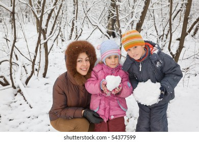 young woman with boy and little girl in winter in wood, children keeps in hands snowballs