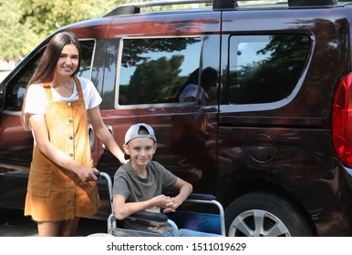 Young woman with boy in wheelchair near van outdoors