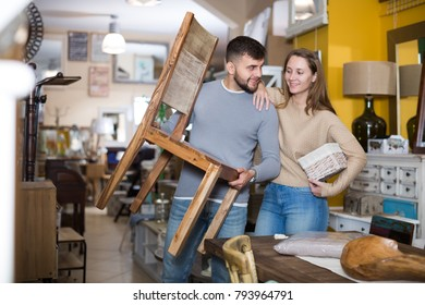 Young woman with boyfriend holding vintage chair in apartment crowded of old furniture