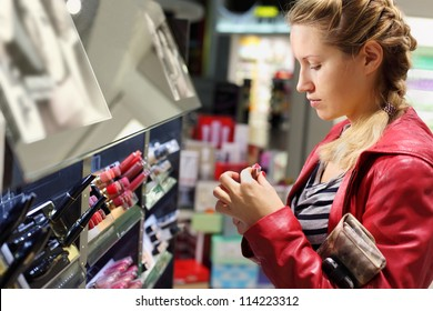 Young woman with braid chooses lipstick in small cosmetics shop.