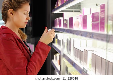 Young woman with braid chooses perfume in small perfume shop.