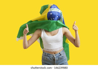 Young woman with Brazilian flag on face gesturing thumbs up over yellow background