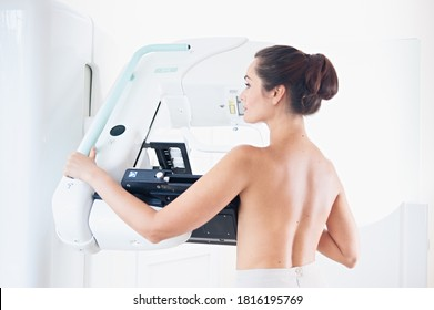 Young woman at breast cancer prevention screening at hospital. Hardware examination of the breast. Healthy young woman doing cancer prophylactic mammography scan. Modern hospital with hi-tech machine