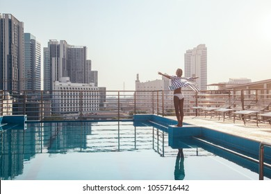 Young woman breathing and enjoying the morning view from roof top infinity pool in Bangkok, Thailand