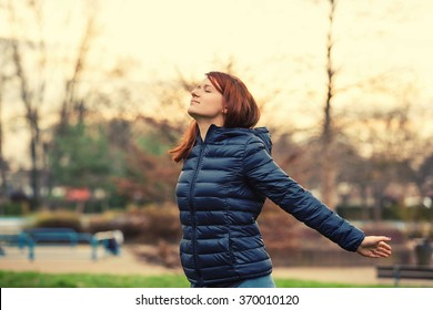 Young woman breathing fresh air before a run.Freedom happy young woman feeling alive and free in a city park in nature with arms raised up.