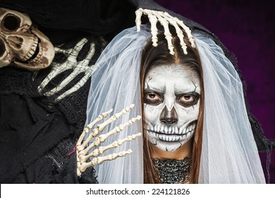 Young woman a bride in a veil day of the dead mask skull face art and skeleton. Halloween face art.