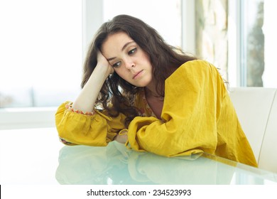 Young woman in bright blouse bored at home