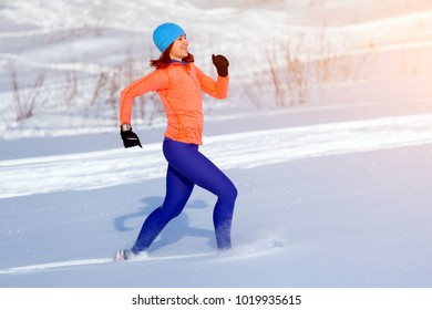 A young woman in a bright blue hat, an orange sweater and elk skirts runs through the winter snow on a bright winter day