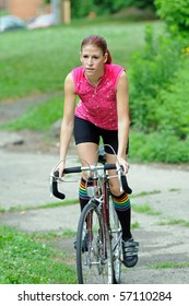 Young woman in bright clothes riding street bike through urban park