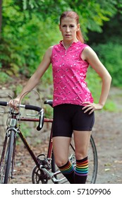 Young woman in bright clothes standing next to street bicycle