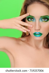 Young woman with bright green makeup on color background