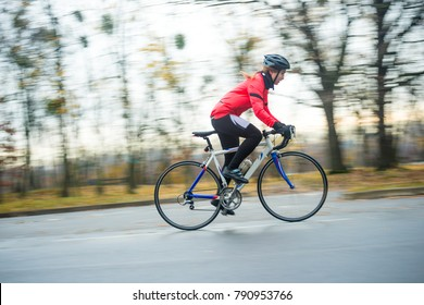 Young Woman in Bright Jacket Riding Road Bicycle in the Park in the Cold Autumn Day. Healthy Lifestyle Concept.