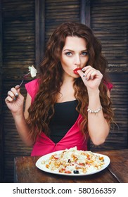 Young woman with bright make up sitting and eating a salad