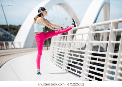 Young woman in bright sportswear exercising outdoors on the white modern bridge in Lyon city
