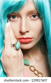 young woman in a bright turquoise wig, indoor
