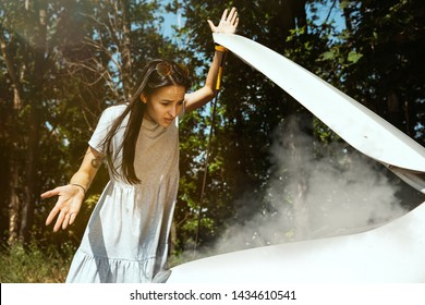 The young woman broke down the car while traveling on the way to rest. She is trying to fix the broken by her own or should hitchhike. Getting nervous. Weekend, troubles on the road, vacation.