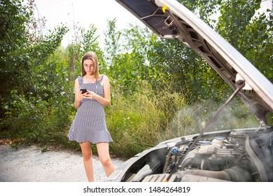 The young woman broke down the car while traveling. She is trying to fix the broken by her own Getting nervous. Weekend, troubles on the road, vacation.
