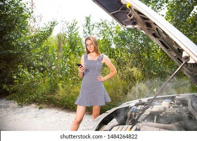 The young woman broke down the car while traveling. Getting nervous. Weekend, troubles on the road, vacation.