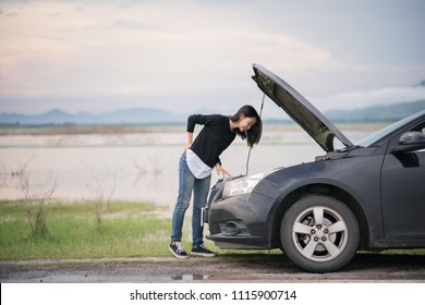 Young woman with a broken car on the road