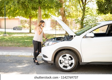 Young woman with a broken car using cell phone to call assistance on roadside
