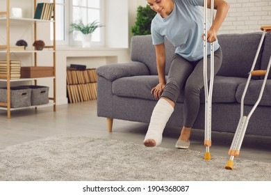 Young woman with broken leg in plaster cast tries to stand up from sofa and walk with crutches at home. Physical injury in domestic or car accident, bone fracture and rehabilitation of people concept
