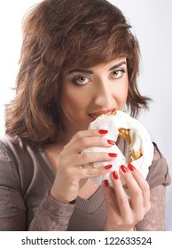 Young woman in brown dress and eating cake with icing