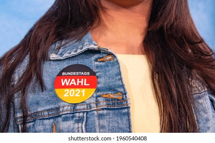 """Young woman with brown hair and an election button for the German federal election on their Jeans jacket , with the inscription: """"Bundestagswahl 2021"""" (Federal Election 2021)."""