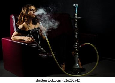 Young woman with brown hair in a hookah. Cloud of smoke