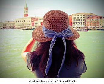 young woman with brown hair and a large straw hat and the great bell tower in Venice  with vintage effect