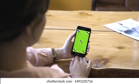 Young woman with brown hair in pink shirt sitting at the wooden table, holding iPhone in hand and looking at the chroma key green screen. Stock footage. Smartphone new technology concept