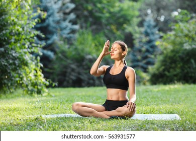 Young woman with brown hair wearing black top and shorts doing yoga position in park, healthy lifestyle, portrait, pranayama.