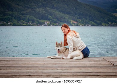 A young woman with brown hair and white sweater is sitting at the pier at the lake with calm water. A Siberian husky female dog is lying down near the girl. The Alps mountains in the background.