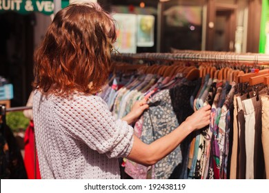 A young woman is browsing a rail of clothes at a street market