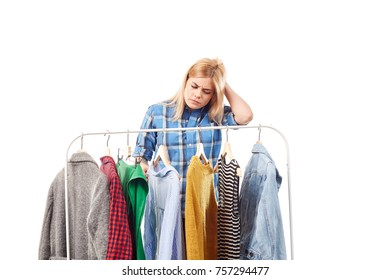 Young woman browsing through clothes on rack