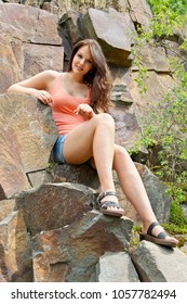 Young woman brunette, 18 years old, near a rock. Shines the bright sun. She is wearing a T shirt and shorts.