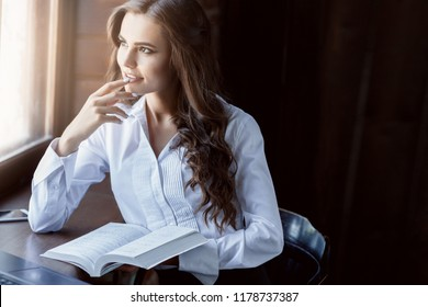 Young woman brunette with curly hair studying with books in library and thinking. Beautiful smiling female student reading book near window. Reading, education,  idea, learning, knowledge concept.